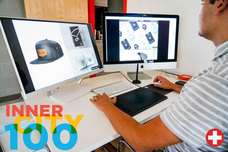 Brand Aid Employee using Mac computer to design merchandise
